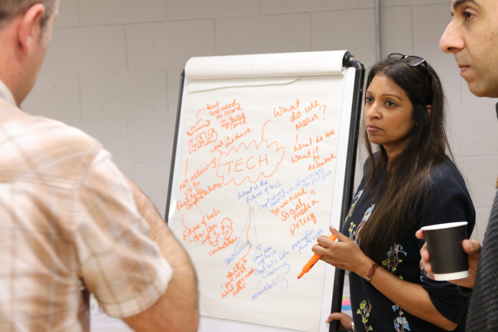 Image of delegates around a flipchart, capturing ideas about technology in learning and development