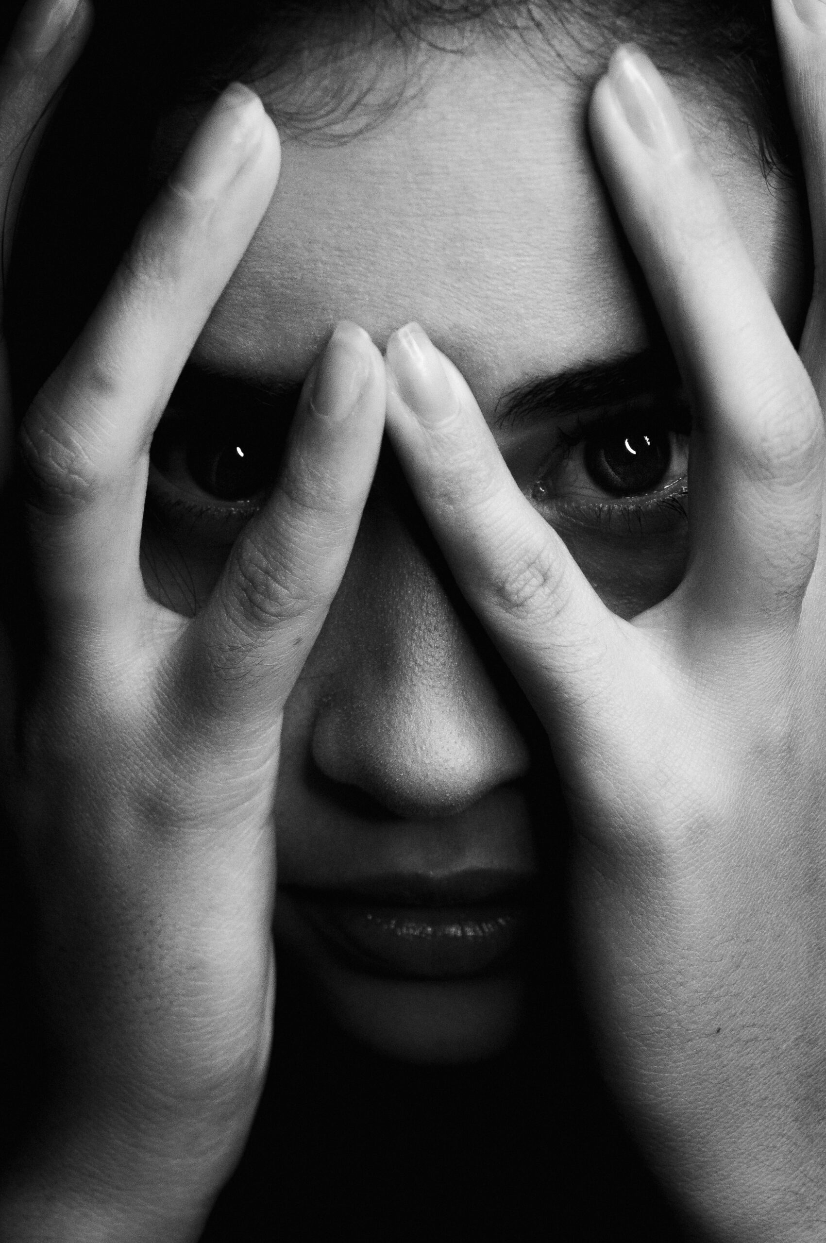 Black and white photo of a woman's face, eyes peaking between the fingers