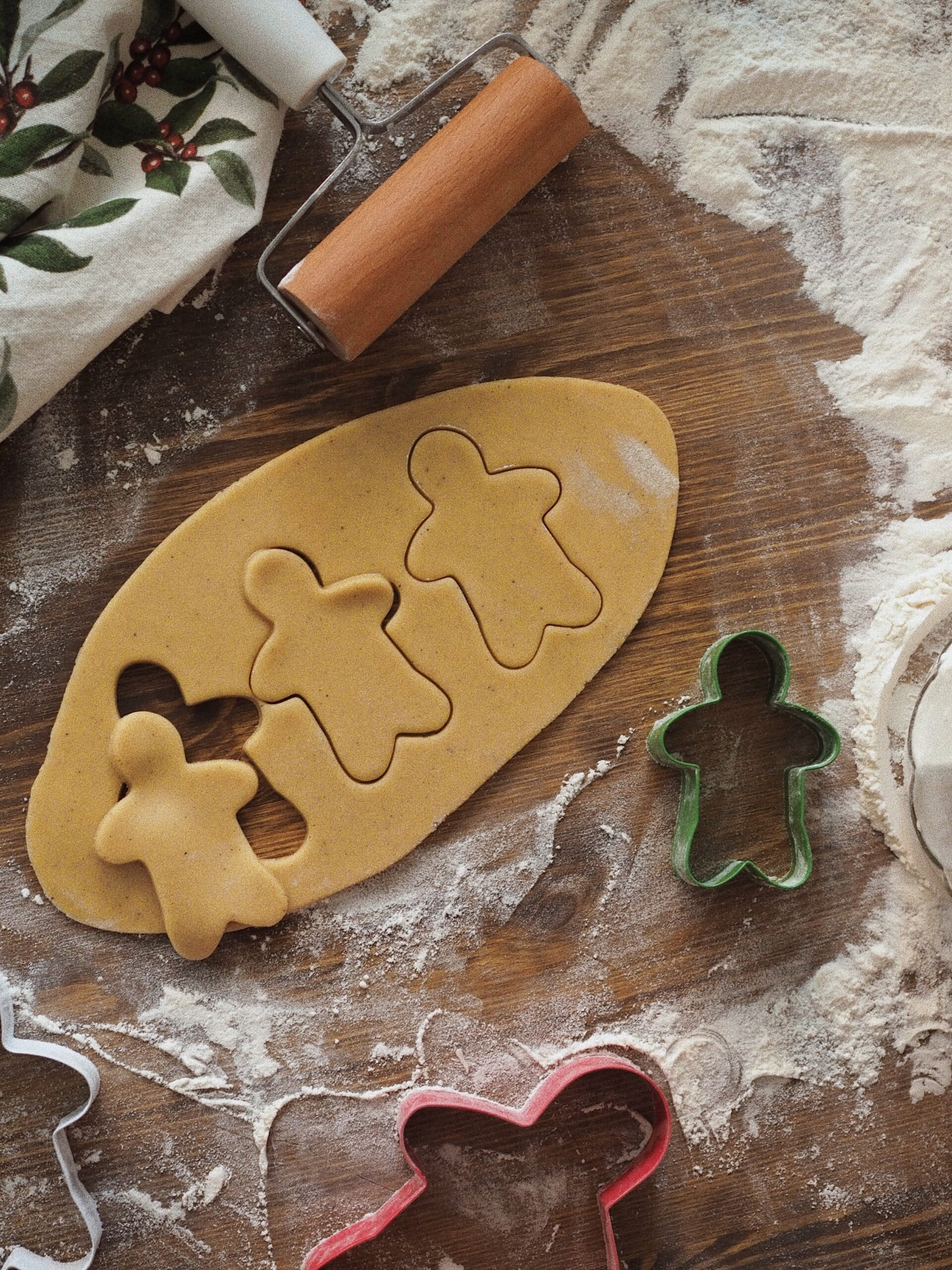 Gingerbread men being cut out of dough with cookie cutters