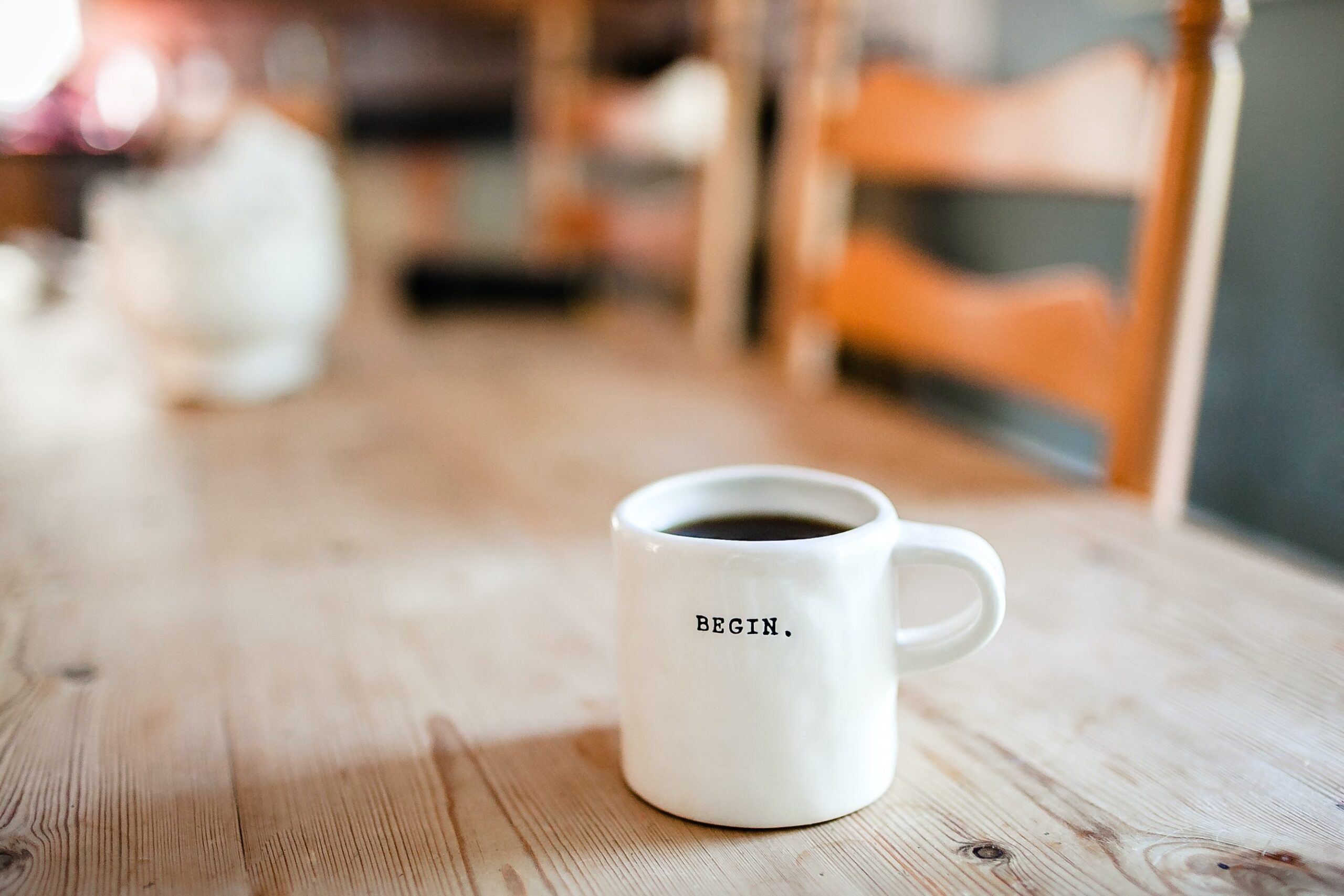 White cup full of black coffee, with 'begin' written in black capitals on the side. On a wooden table with wooden chairs.