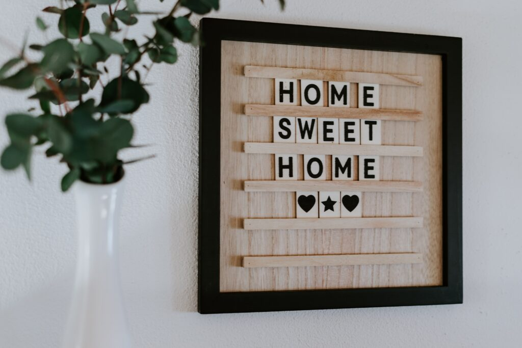Wooden board with home sweet home written in block letters and two black hearts next to a plant
