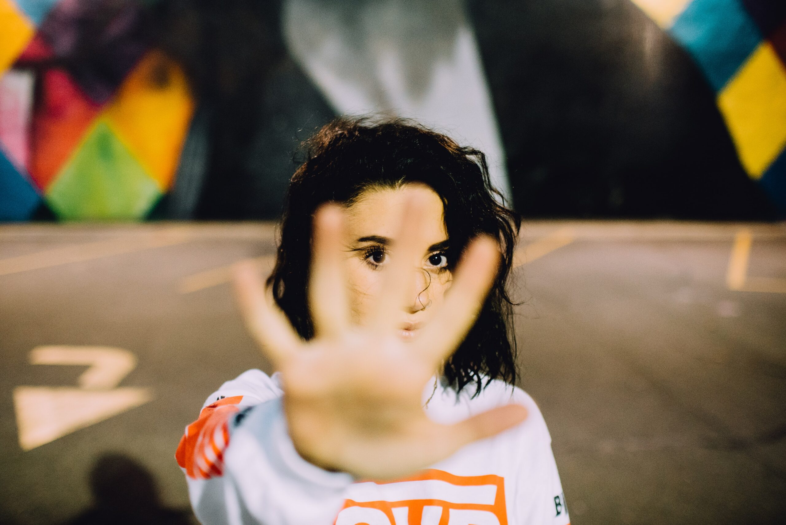 Woman with hand up in front of her, indicating no. Stop.