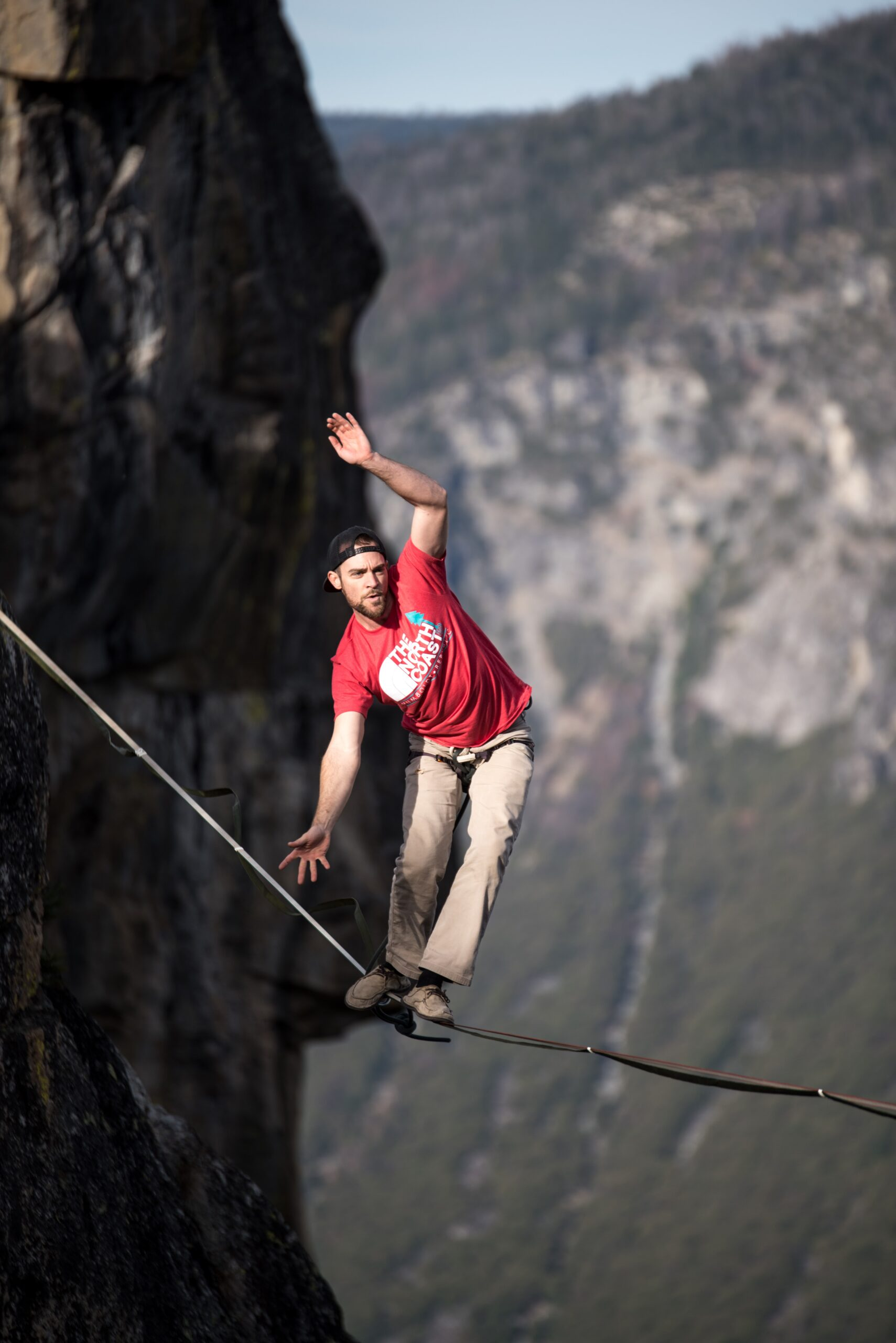 Man in red t-shirt trying to get balance on a tightrope.